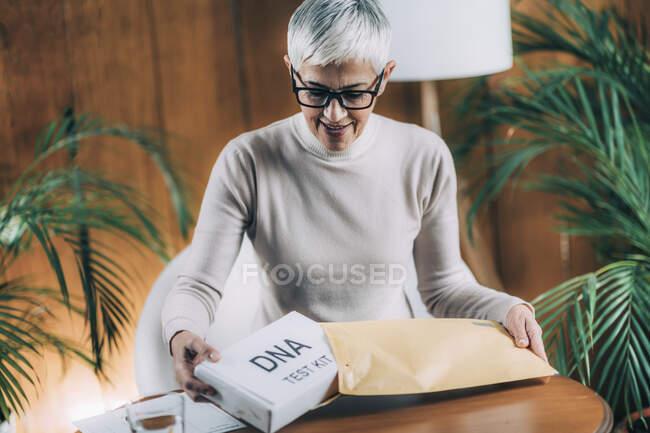 Senior woman preparing DNA test kit. — Stock Photo