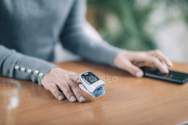 Senior woman using pulse oximeter and smart phone, measuring oxygen saturation. — Stock Photo
