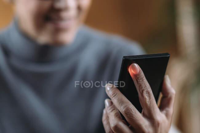 Пожилая женщина измеряет пульс или частоту сердечных сокращений с помощью смартфона. — стоковое фото