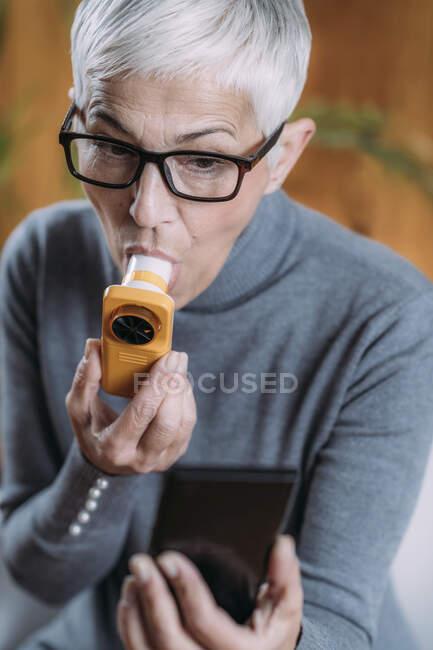 Senior woman using spirometer, measuring lung capacity and peak expiratory force. — Stock Photo