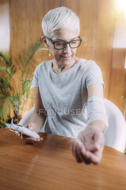 Senior woman doing elbow physical therapy with TENS (transcutaneous electrical nerve stimulation) electrode brace pads. — Stock Photo