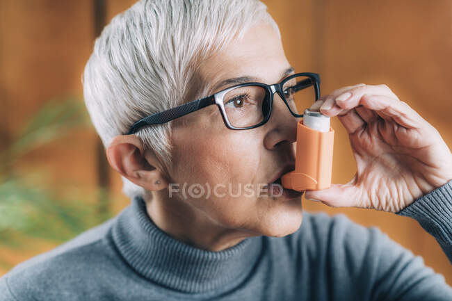 Senior woman inhaling medicine from asthma pump. — Stock Photo