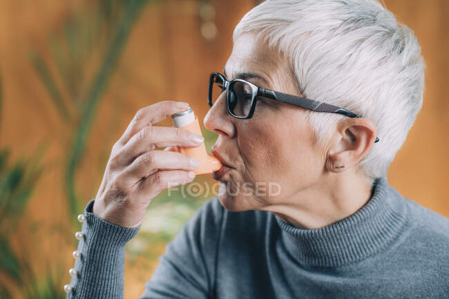 Senior woman using asthma inhaler with extension tube. — Stock Photo