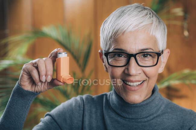 Inhaling medicine. Senior woman using an inhaler with extension tube. — Stock Photo
