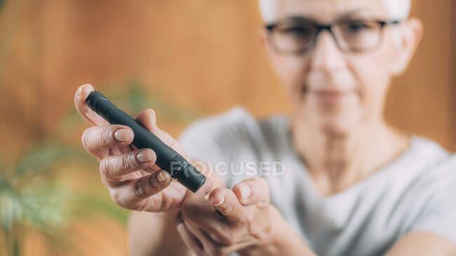 Женщина, делающая анализ крови на глюкозу — стоковое фото