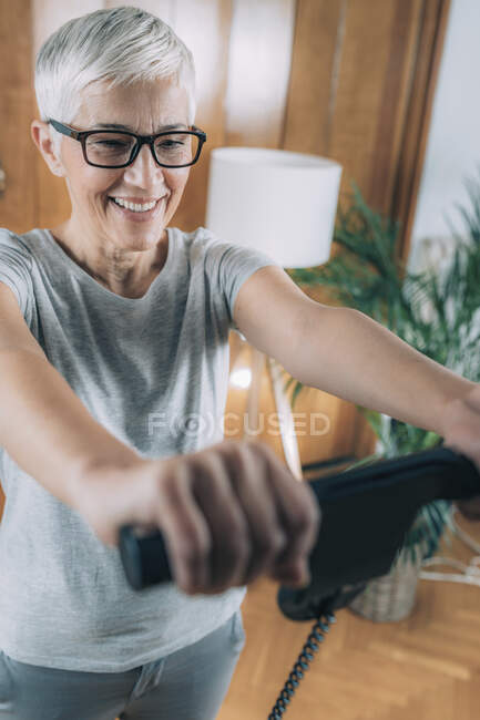 Cheerful senior woman measuring body composition with digital scale monitor at home. — Stock Photo