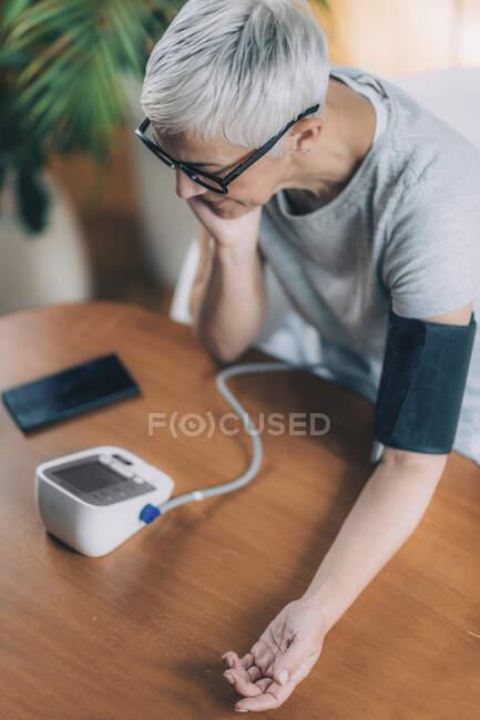 Мобильное здравоохранение. Измерение артериального давления и ввод данных в смартфон. — стоковое фото