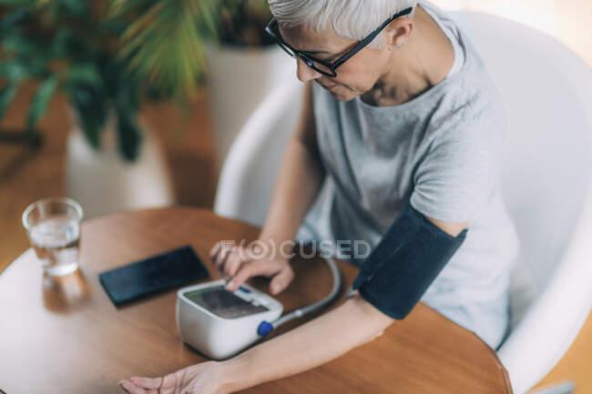 Senior woman using blood pressure meter. — Stock Photo