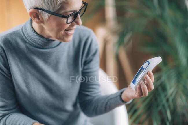 Посмішка Старша жінка вимірює температуру тіла за допомогою неконтактного цифрового термометра. — стокове фото