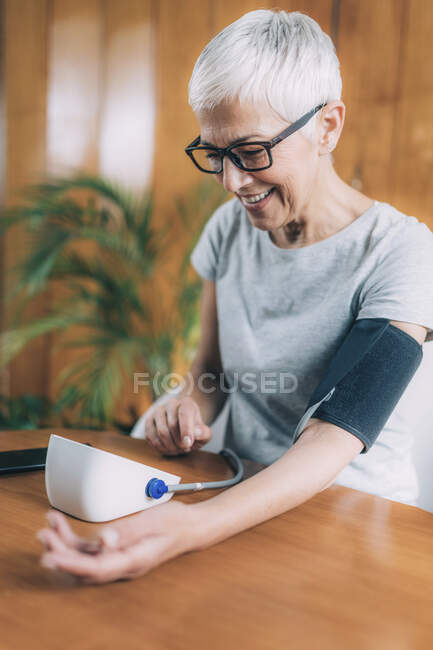 Measuring blood pressure and using smart phone to follow results. — Stock Photo