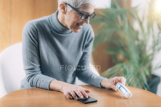 Senior woman recording body temperature with non-contact digital thermometer, using smart phone app. — Stock Photo