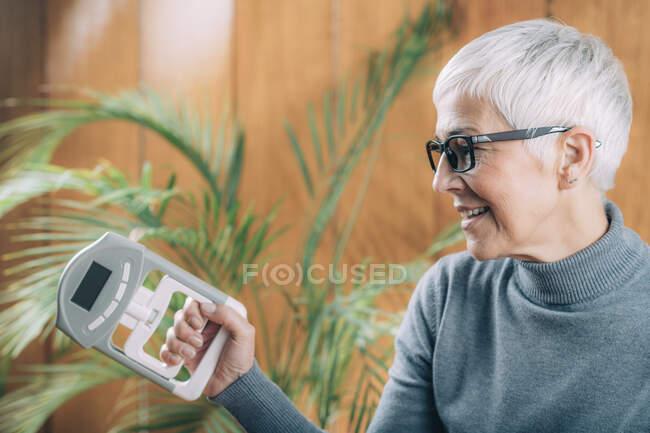 Senior woman with digital hand grip dynamometer, measuring strength. — Stock Photo