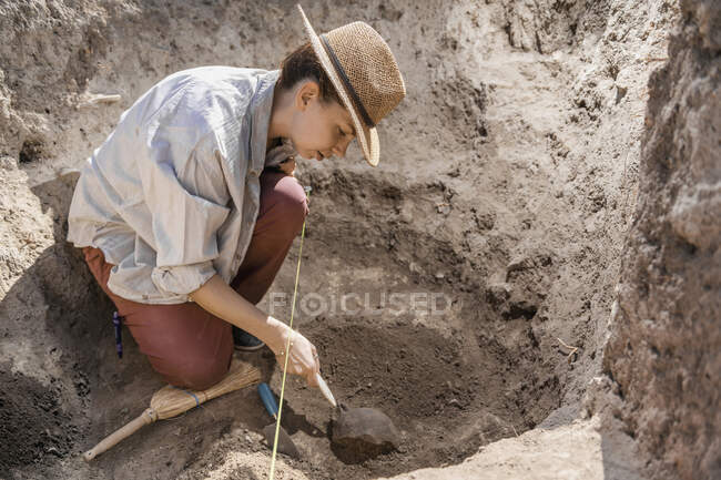 Archaeologist digging with hand trowel, recovering pottery from an archaeological site. — стокове фото