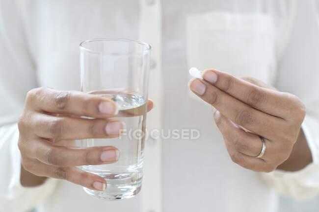 Mujer tomando una pastilla con un vaso de agua. - foto de stock
