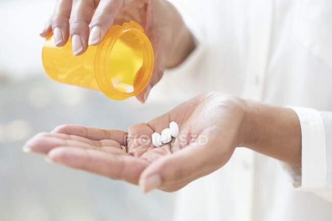Mulher derramando pílulas em sua mão. — Fotografia de Stock