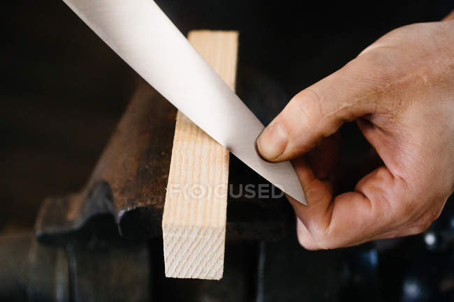 Artisan working with knife in workshop — Stock Photo