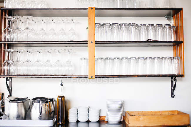 Glasses on shelves and tableware — Stock Photo