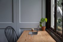 Laptop on wooden desk with credit card in home interior. — Stock Photo