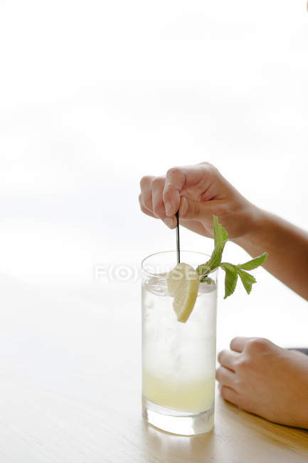 Female hands putting lemon in glass — Stock Photo