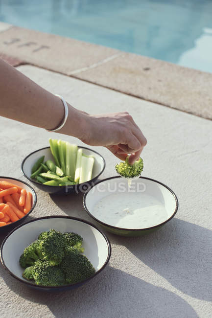 Woman dipping cooked vegetables in sauce — Stock Photo