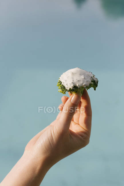 Female hand holding piece of broccoli — Stock Photo