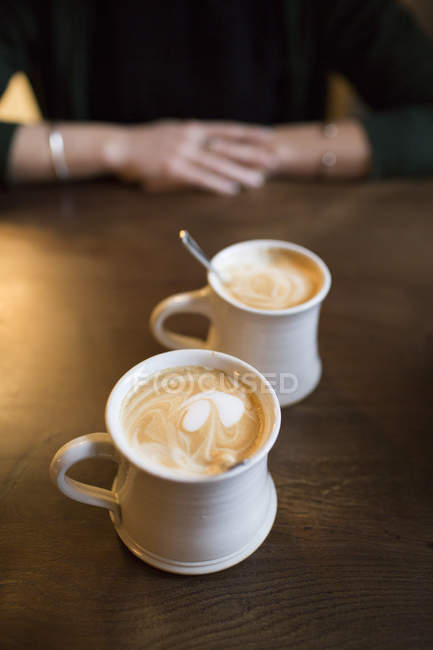 Two coffee lattes in white clay mugs — Stock Photo