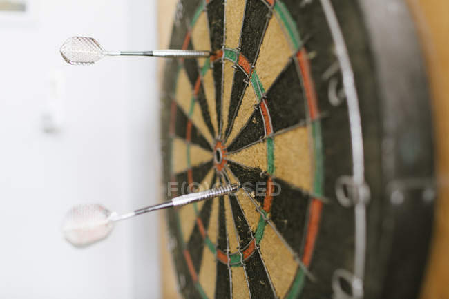 Two darts sticking in dartboard — Stock Photo