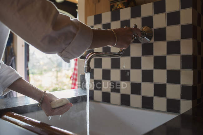 Woman washing hands at sink in kitchen — Stock Photo