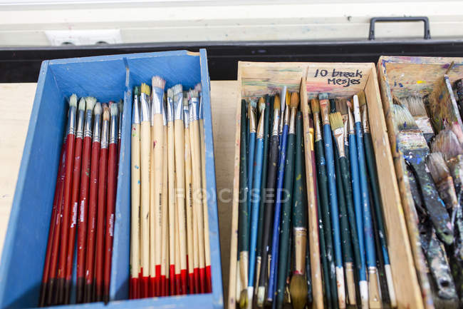 Paint brushes in wooden cases — Stock Photo