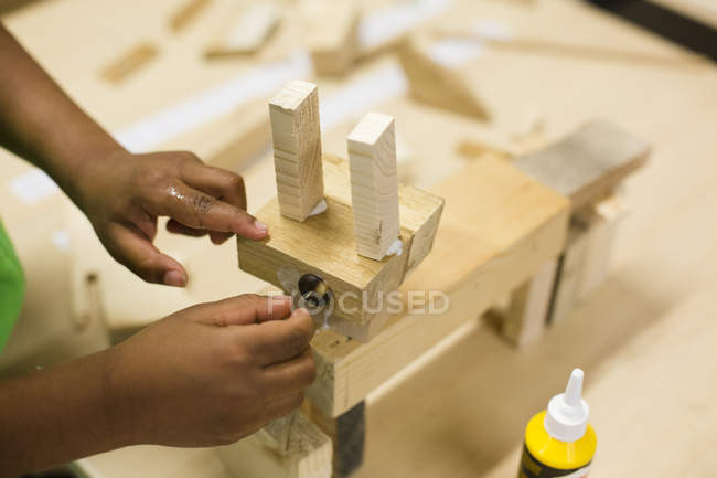 Childish hands assembling wooden toy — Stock Photo
