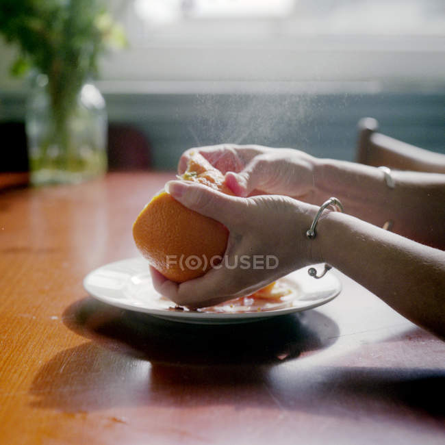 Female hands Peeling orange — Stock Photo