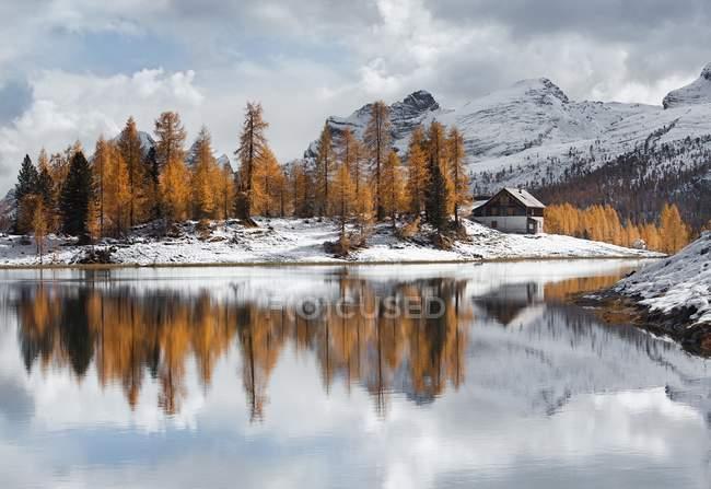 Чистою водою озера, дерев та засніжених схилах — стокове фото
