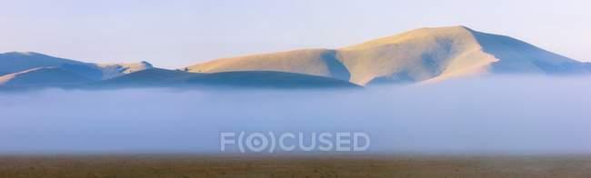 Brouillard et les nuages à l'aube du Sibillini meadows, Parc National des monts Sibillini, Italie — Photo de stock