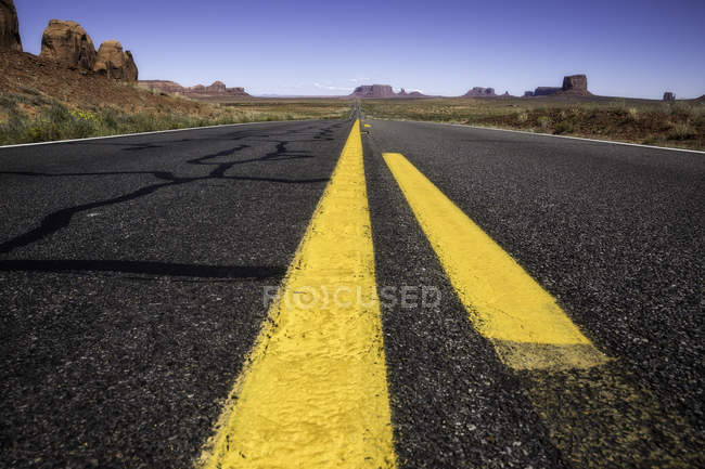 Carretera interestatal cruzando llanuras áridas de Monument Valley - foto de stock
