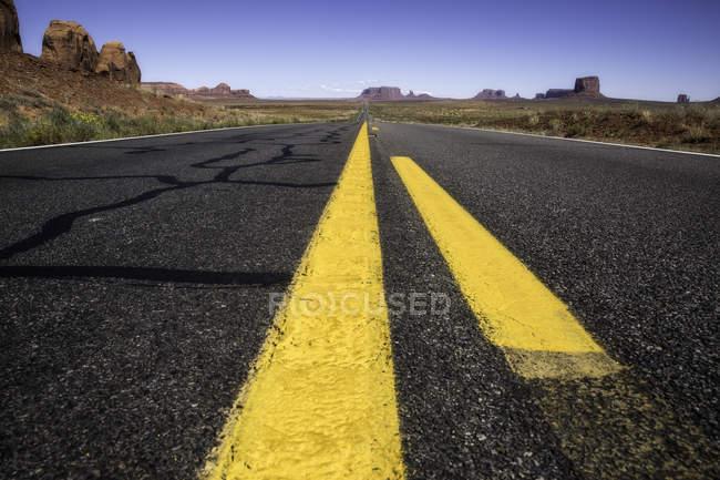 Estrada interestadual cruzando planícies áridas do Monument Valley — Fotografia de Stock