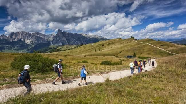 Hikers along the path of Pralongi medows — Stock Photo
