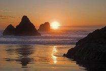 Orange coucher de soleil derrière les rochers au large — Photo de stock