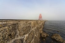 Red lighthouse in fog on coast — Stock Photo