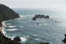 Sandy beach on base of cliff — Stock Photo