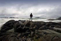 Man standing on stones against water — Stock Photo