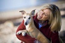 Женщина в теплой одежде и собака — стоковое фото
