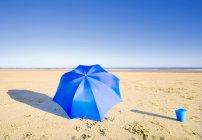Guarda-chuva e balde na praia — Fotografia de Stock