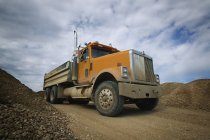 Caminhão de cascalho na estrada de terra — Fotografia de Stock