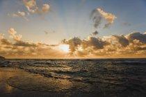 Coup de soleil à travers les nuages sur l'eau — Photo de stock