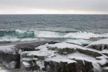 Des roches couvertes de vagues qui s'écrasent contre la glace — Photo de stock