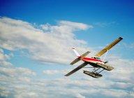 Un aeroplano nel cielo contro le nubi — Foto stock