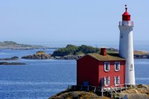 Lighthouse with small red house — Stock Photo