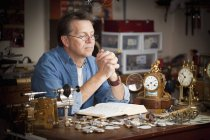 A Clock Maker Prays At His Desk In His Shop — Stock Photo