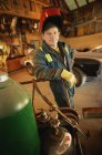 Portrait of male welder standing in front of car — Stock Photo