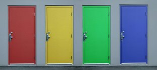 Set of colorful doors in grey wall — Stock Photo